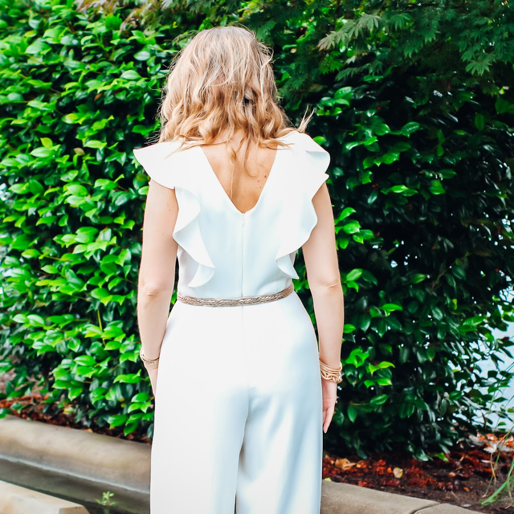 Laura Mintz with Illuminate Blog styles a ruffle sleeve white jumpsuit with gold jewelry, Valentino studded heel dupes and a classic red lip.  Perfect for work or play.