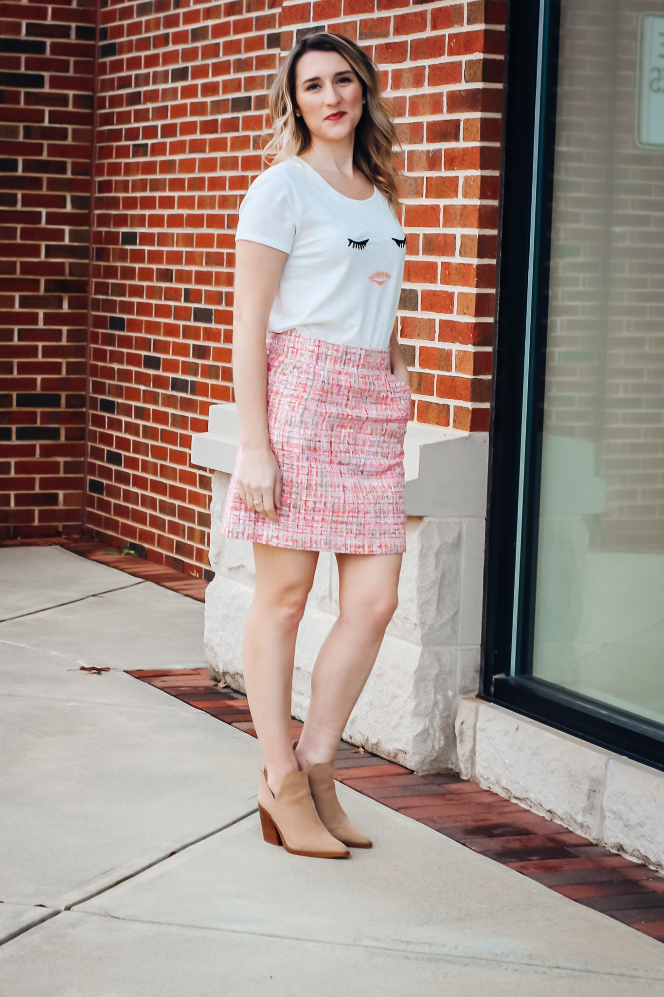 Pink Tweed Skirt styled with eyes and lips graphic tee and tan booties